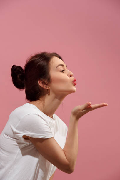 Portrait of attractive cute girl with bright makeup with kiss isolated over pink background I kiss you. Portrait of attractive woman with kiss on lips. Pink studio. Beautiful female portrait. Young happy emotional funny woman looking at camera. Human facial emotions concept. Profile pecking stock pictures, royalty-free photos & images