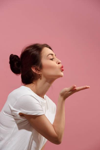 portret van aantrekkelijke schattig meisje met lichte make-up met kus geïsoleerd op roze achtergrond - zoen stockfoto's en -beelden