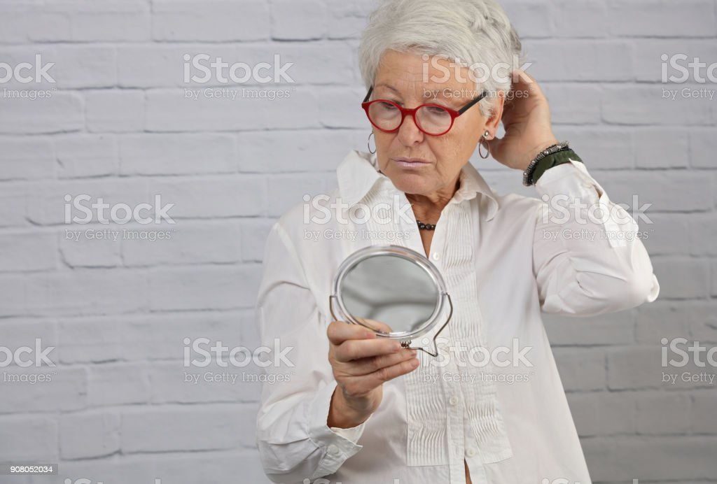 Portrait Of Attractive Elderly Woman Holding A Mirror Older