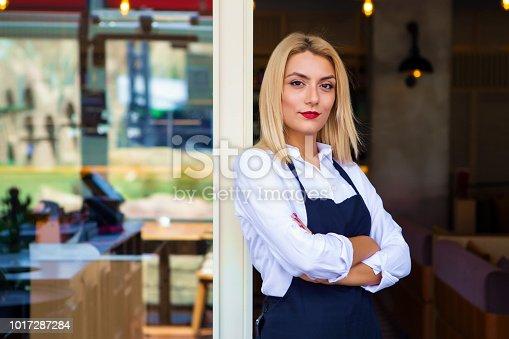 1066358064istockphoto Portrait of attractive female barista working in cafeteria 1017287284