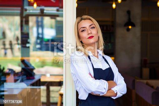 1066358064istockphoto Portrait of attractive female barista working in cafeteria 1017287336