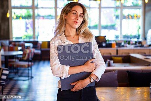 1066358064istockphoto Portrait of attractive female barista working in cafeteria 1017287628