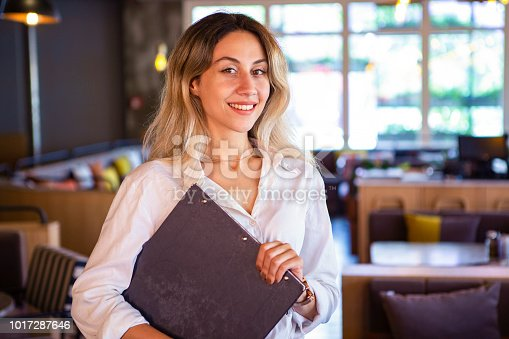 1066358064istockphoto Portrait of attractive female barista working in cafeteria 1017287646
