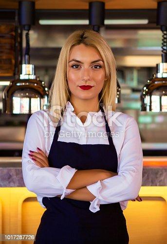 1066358064istockphoto Portrait of attractive female barista working in cafeteria 1017287726
