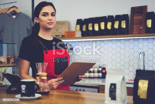 istock Portrait of attractive female barista working in cafeteria 693694096