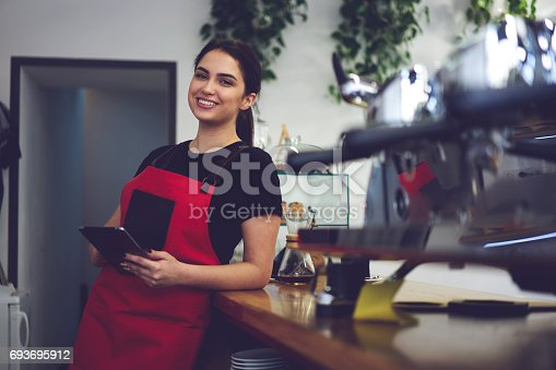 istock Portrait of attractive female barista working in cafeteria 693695912