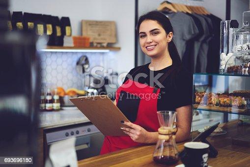 istock Portrait of attractive female barista working in cafeteria 693696180