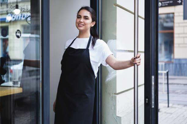 Retrato de atractiva mujer barista en cafetería - foto de stock