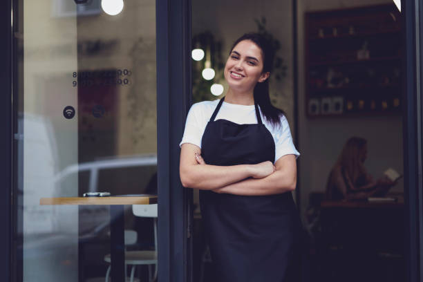 portrait of attractive female barista working in cafeteria - apron stock pictures, royalty-free photos & images