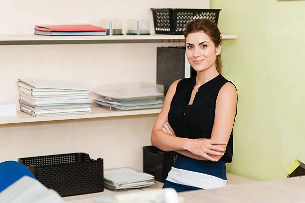 портрет привлекательная женщина сидит на офисный стол, улыбающегося. - vlad models стоковые фото и изображения