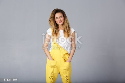 1092709104 istock photo Portrait of attractive female with charmong smile in denim casual yellow overall being in good mood. American caucasian woman with curly long hair have positive emotions. People, human, person 1176341107