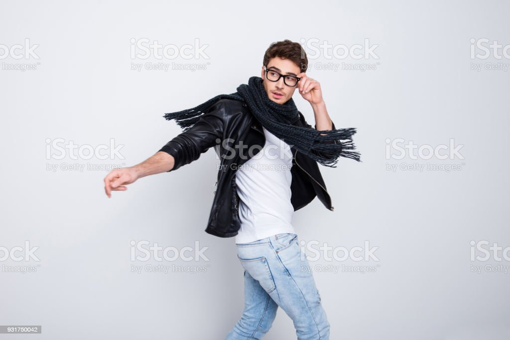 Portrait of attractive, harsh, stylish guy in motion with scarf around his neck, holding eyelet of glasses on his face with fingers looking back side, isolated on grey background stock photo