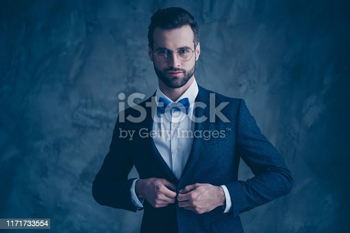 istock Portrait of attractive man fixing his modern blazer looking through eyewear eyeglasses isolated over gray background 1171733554