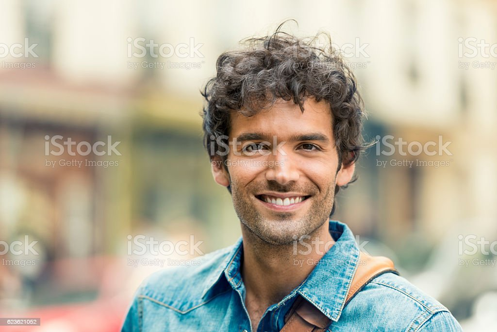 Portrait of attractive man wearing jeans shirt. City background stock photo