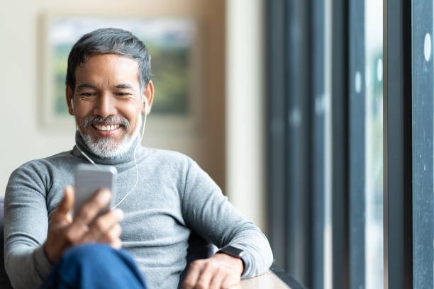 Portrait of attractive mature asian man retired with stylish short beard using smartphone sitting or listening music in urban lifestyle coffee shop. Old man using social network internet technology. stock photo
