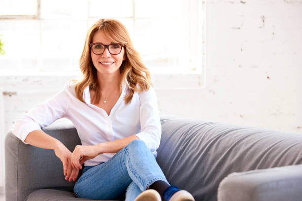Cтоковое фото Portrait of attractive middle aged woman relaxing on sofa