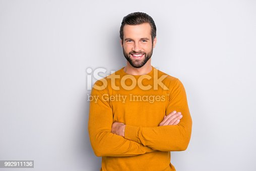 istock Portrait of attractive self-assured with beaming shiny smile haircut with long furfur wearing casual classic color of mustard sweater macho man standing with folded arms isolated on gray background 992911136