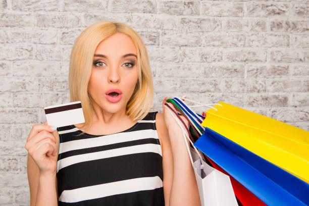 porträt von attraktiven shopper mit bankkarte und päckchen mit kleidung - geld schön verpacken stock-fotos und bilder