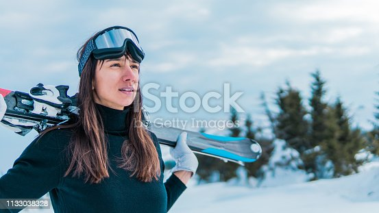 Portrait of attractive skier with ski goggles holding skies