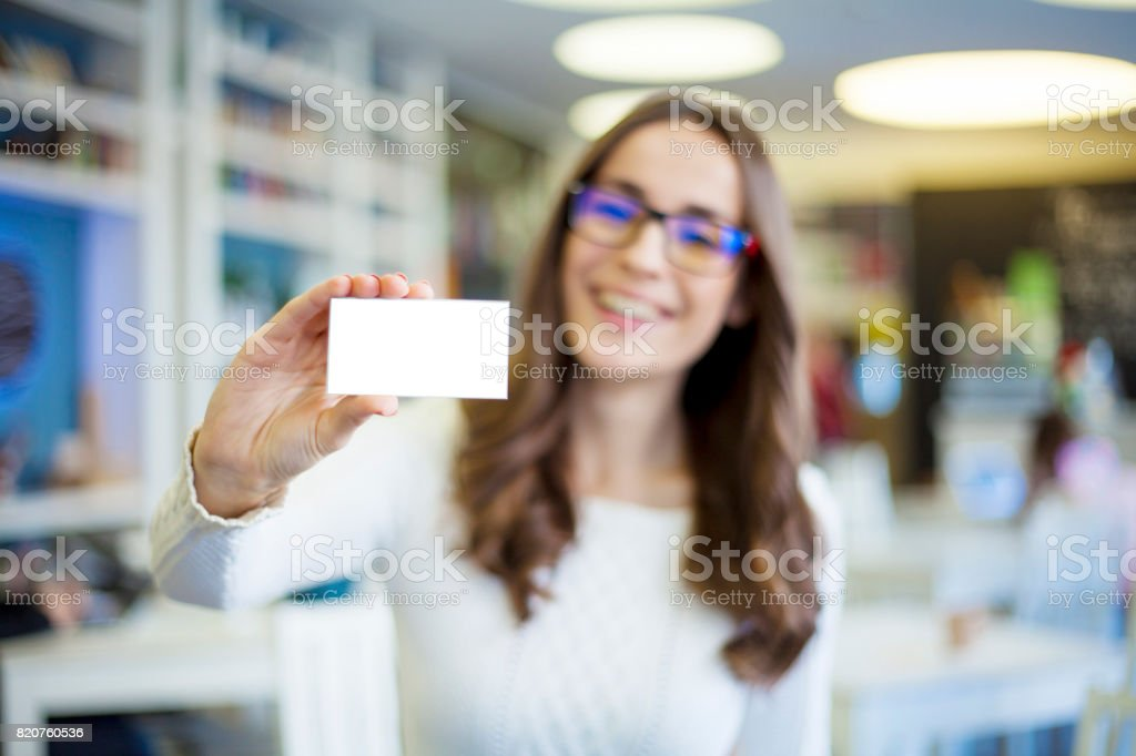 Portrait of attractive smiling brunette business woman in glasses with visit card in hand stock photo