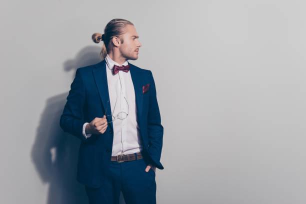 porträt von attraktiven atemberaubenden mann hält seine brille in der hand und ein weiteres in tasche, wandte sein gesicht zur seite, stand über grauen hintergrund - hochzeitsanzug herren stock-fotos und bilder