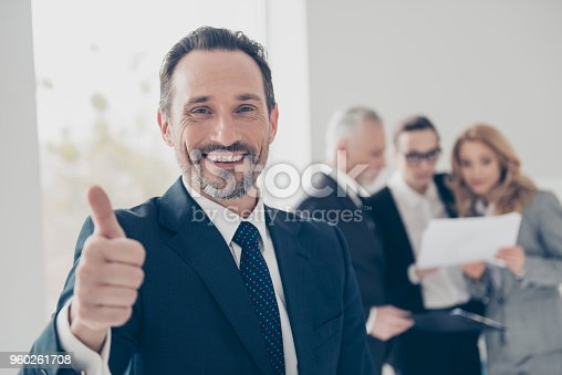 istock Portrait of attractive, stylish, confident, brunet director with stubble in tux with tie showing thumb up with finger looking at camera, colleagues discuss project on blurred background 960261708