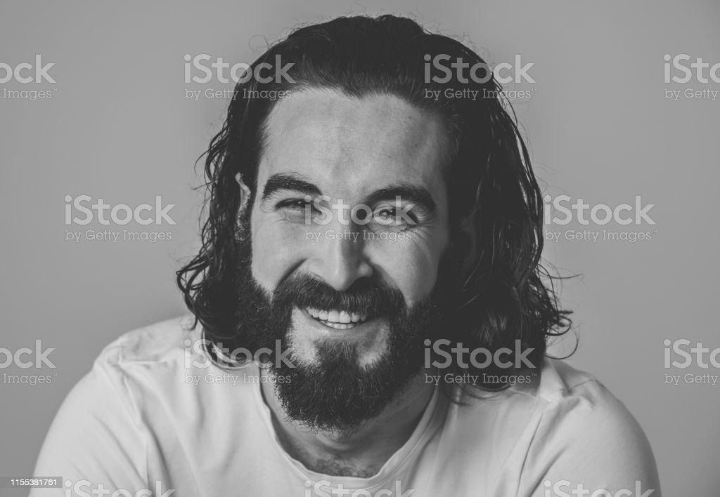 Portret van aantrekkelijke stijlvolle mode man in zijn 20s op zoek naar sexy met baard, lang donker haar en bruine ogen. Mannelijke hipster model poseren tegen neutrale achtergrond. In People en Beauty concept. - Royalty-free 20-29 jaar Stockfoto
