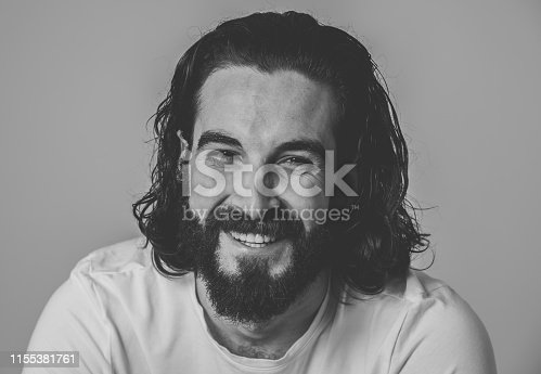istock Portrait of Attractive stylish fashion man in his 20s looking sexy with beard, long dark hair and brown eyes. Masculine hipster model posing against neutral background. In People and Beauty concept. 1155381761