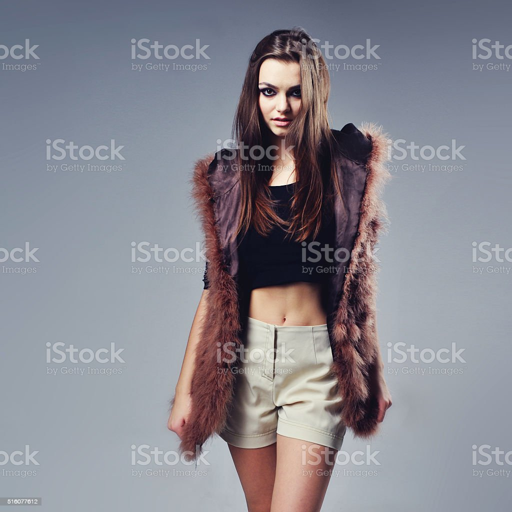Portrait of attractive stylish woman in fur against grey background. stock photo