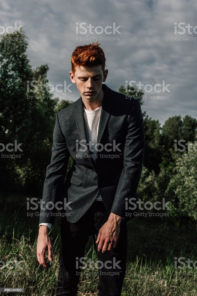 Portrait of attractive stylish young guy model with red hair and freckles standing on green grass, wearing jacket. Fashionable outdoor shot. stock photo