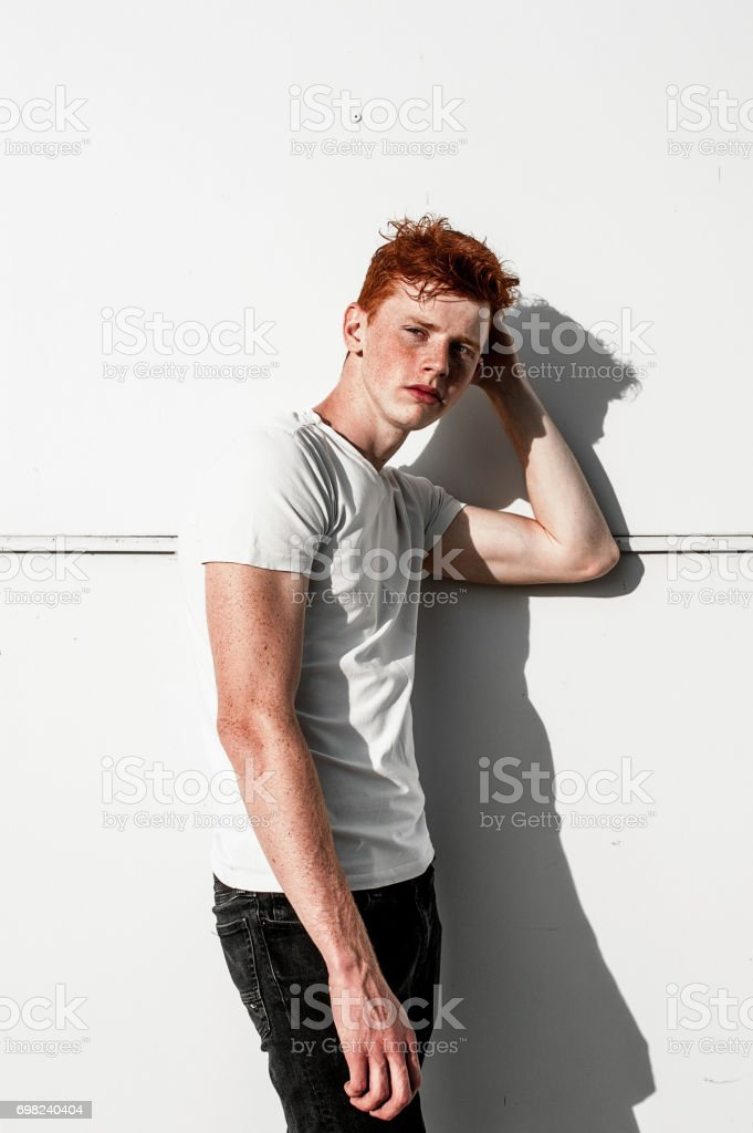 Portrait of attractive stylish young guy model with red hair and freckles standing near white wall , wearing white t-shirt. Fashionable outdoor shot. stock photo