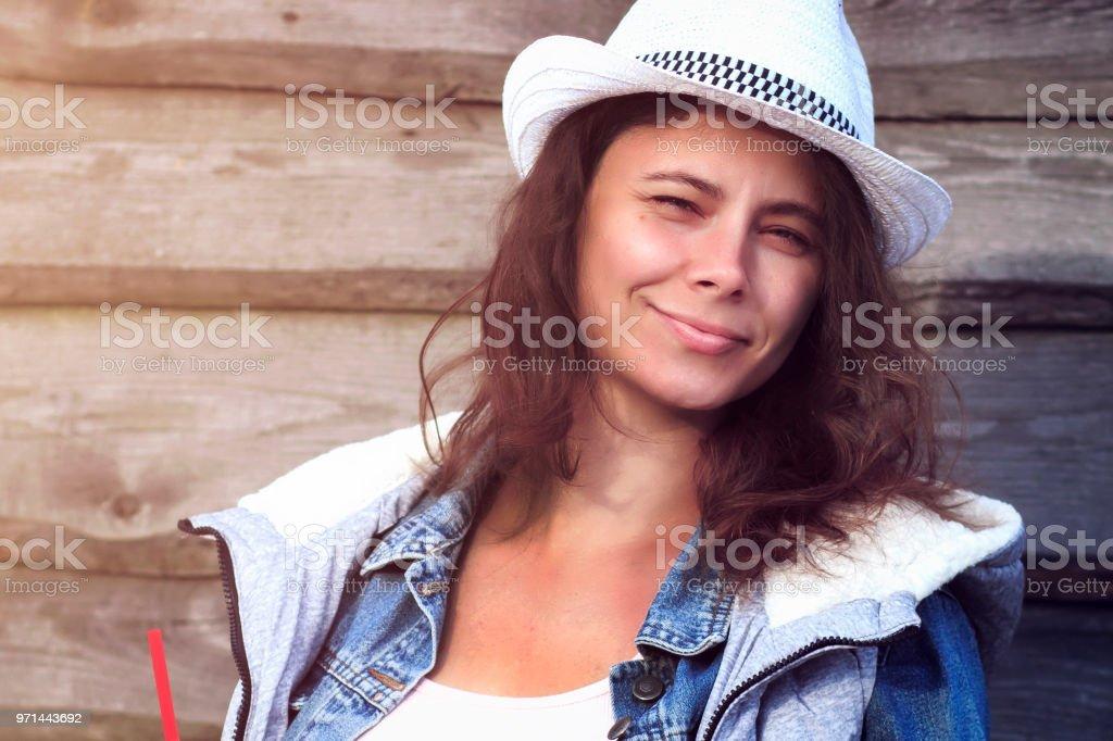 78a560bb527eb Portrait de la belle jeune femme bronzée en chapeau de cowboy contre une  barrière en bois