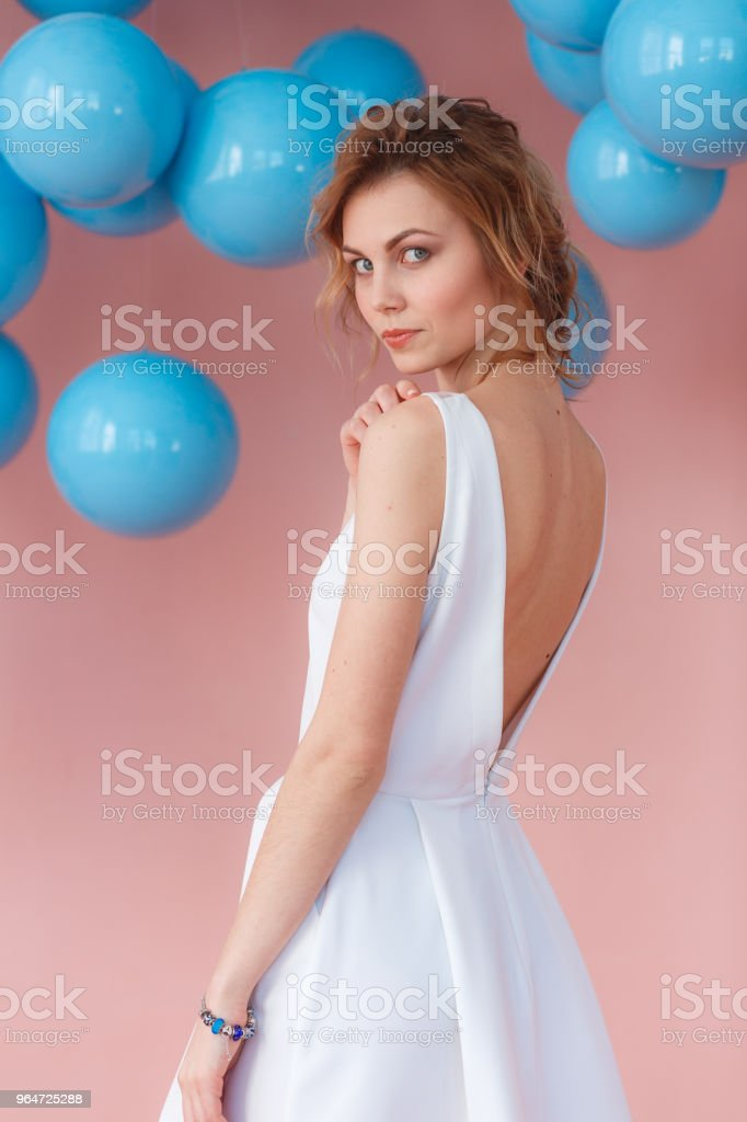 Portrait of attractive tender gentle beautiful fashionable girl with short haircut wearing white evening dress with naked shoulders, isolated on pink background, copy space royalty-free stock photo