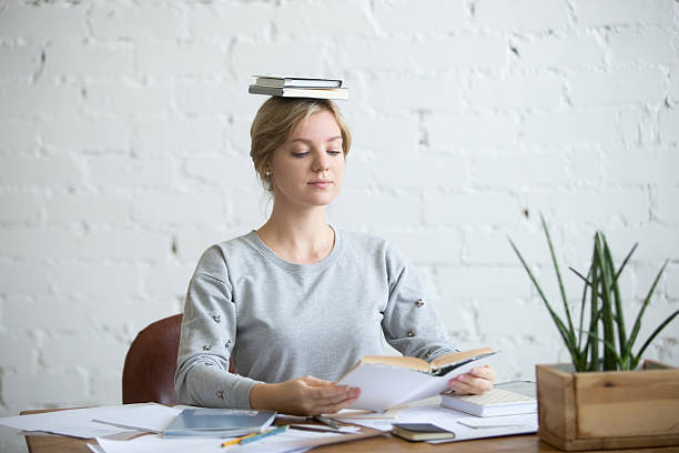 portrait of attractive woman at desk, books on her head - gerade stock-fotos und bilder