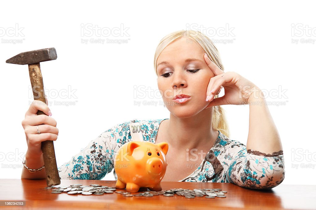 Portrait of attractive woman thinking to break a piggy bank. royalty-free stock photo