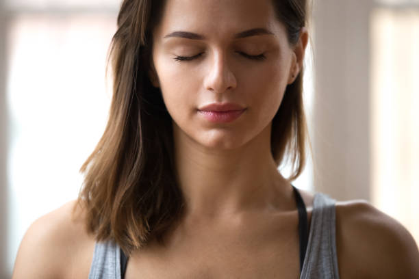 Portrait of attractive yogi woman meditating, close up Portrait of attractive woman meditating with eyes closed, female doing restorative yoga exercise, lady relaxing after training at home or studio, stress relief breathing technique. Well-being concept deep stock pictures, royalty-free photos & images