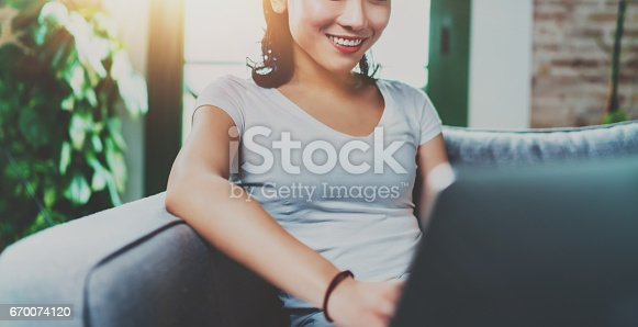 istock Portrait of attractive young Asian woman sitting at sofa and working modern laptop at home, wearing white tshirt.Horizontal, blurred backgroung, flare effect.Wide, crop. 670074120