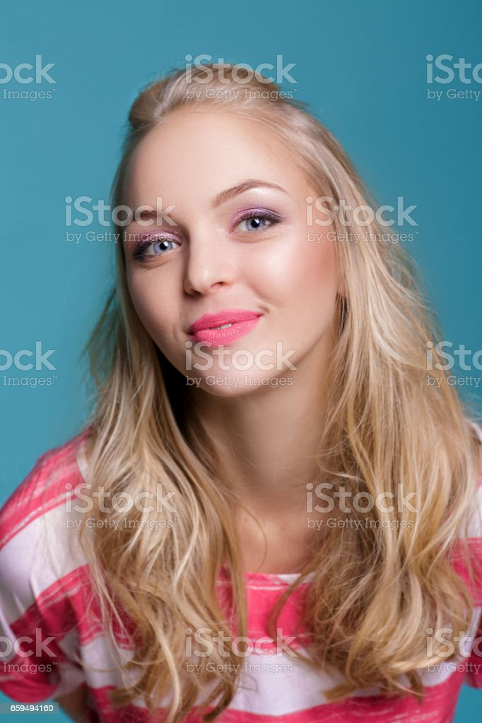2afcc8c24c628 Portrait of attractive young blond woman in pink blouse on blue background  - Stock image .
