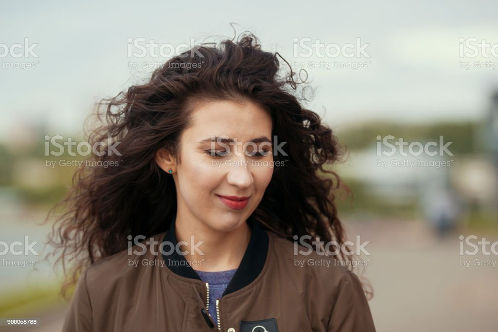 Porträtt av attraktiv ung brunett kvinna med långt lockigt hår - Royaltyfri Apelsin Bildbanksbilder