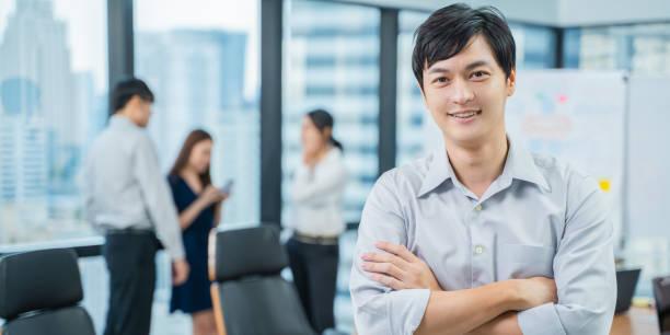 Un retrato de atractivo joven empresario en la oficina moderna con gente de negocios detrás, estilo de vida de oficina de la gente asiática, banner horizontal para el diseño del sitio web - foto de stock