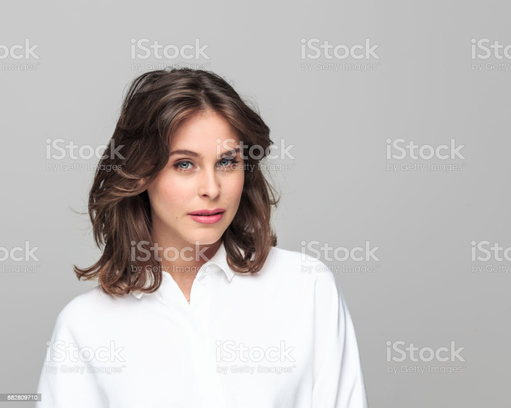 Portrait of attractive young businesswoman Portrait of attractive young businesswoman looking at camera against grey background with copy space. 25-29 Years Stock Photo
