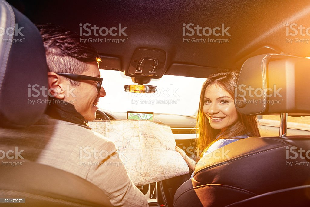 Portrait of attractive young couple driving and looking at map stock photo