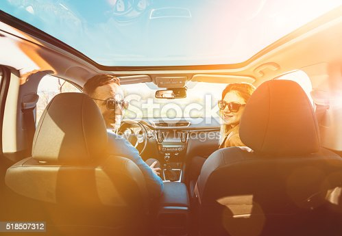 Portrait of modern, good looking guy and his girlfirend in the luxury white car driving with sunroof through nature and travelling in sunset. Couple looking into camera and holding steering wheel and driving. Image taken in Europe, with two caucasian models, taken with Nikon D800 and 16-35mm pro lens, developed from RAW in XXXL size. Location, Europe, Serbia