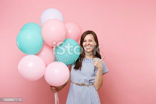 28c29ef6d 1005612630istock Retrato de feliz joven atractivo vestido azul sosteniendo  globos coloridos mostrando pulgar arriba aisladas sobre