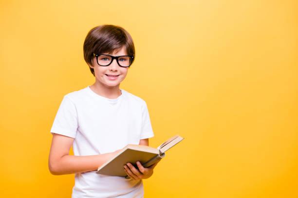 porträt von attraktiven kleine fröhliche schuljunge, lächeln, das tragen einer brille lesen eines buches auf gelbem hintergrund, isoliert. textfreiraum - geek t shirts stock-fotos und bilder