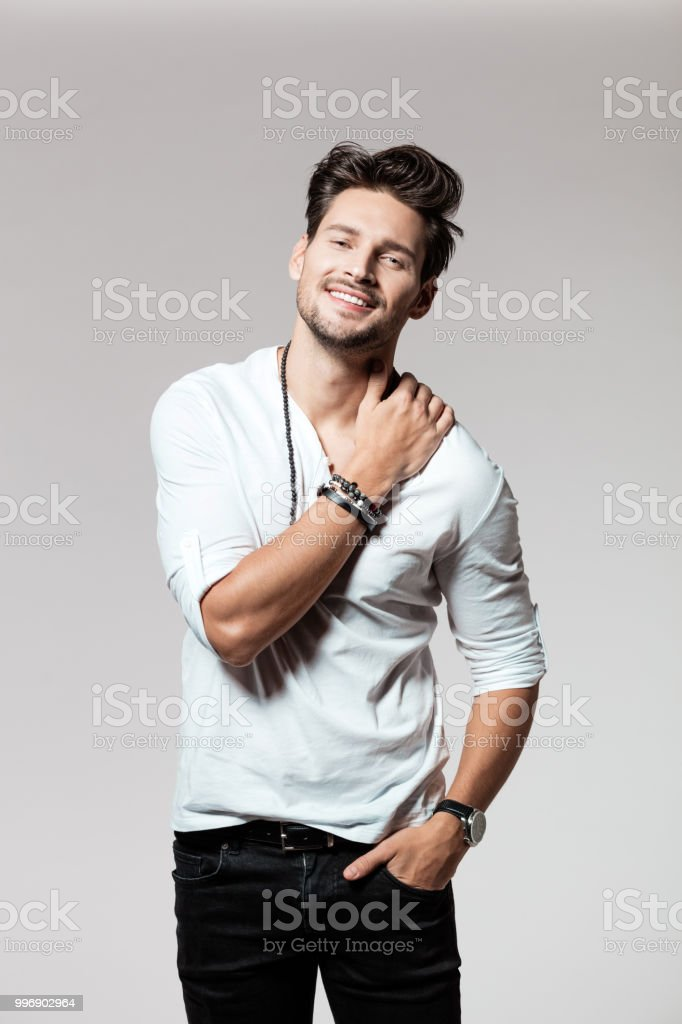 Portrait of attractive young man Portrait of attractive young man standing over grey background and smiling 25-29 Years Stock Photo