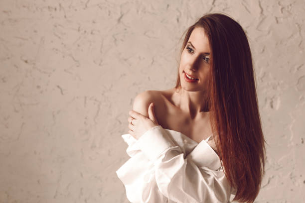 Portrait of attractive young redhead woman with long hair sitting in man's shirt stock photo