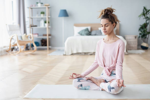 Portrait of attractive young woman working out at home, doing yoga exercise on white mat. stock photo