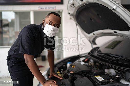 Portrait of auto mechanic man with face mask at auto repair shop