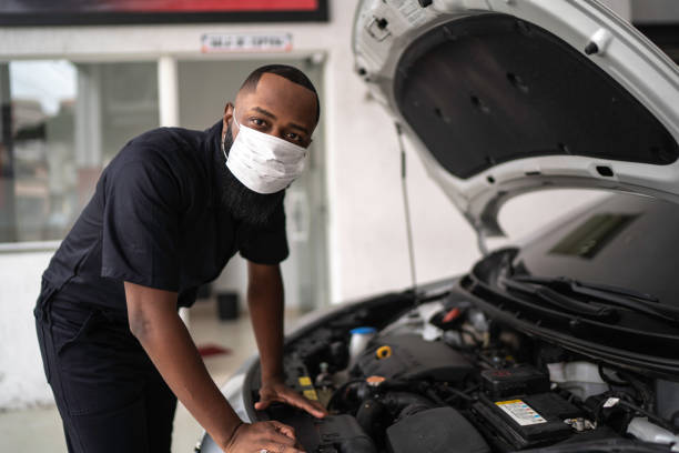 Portrait of auto mechanic man with face mask at auto repair shop stock photo